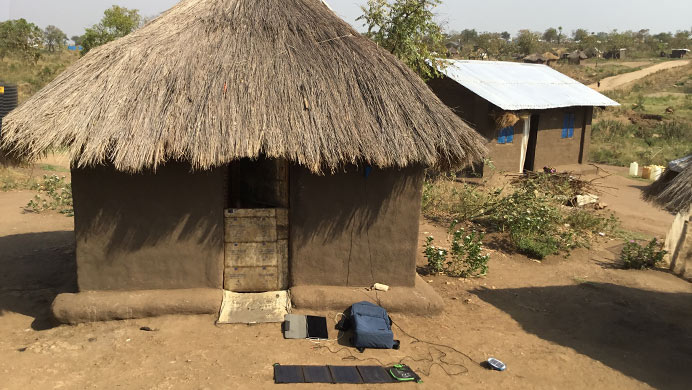 Project Backpack equipment including a solar panel and a tablet, in front of a home
